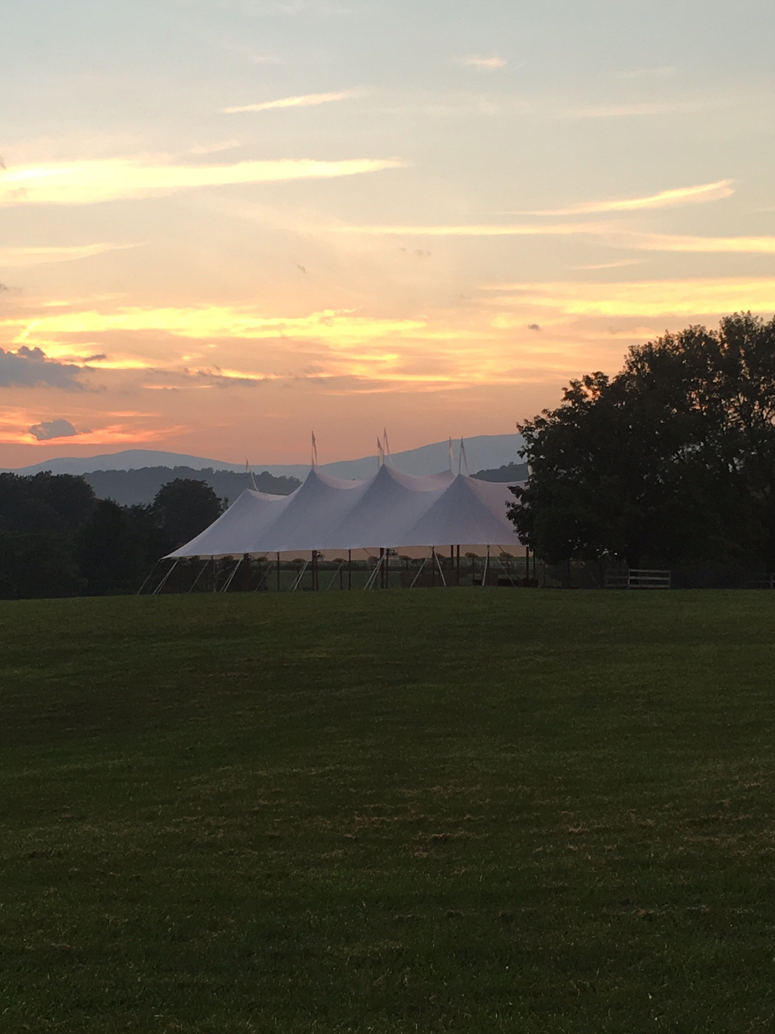 Tent in front field with sunset.txt